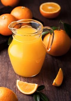 Glaskruik organisch vers jus d'orange met ruwe sinaasappelen op donkere houten achtergrond