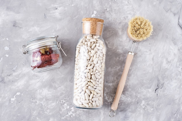 Glaskruiken met voedselingrediënten op een grijze achtergrond, hoogste mening. geen afvalconcept. keukenachtergrond met milieuvriendelijke werktuigen