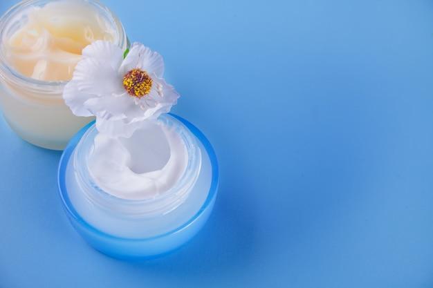 Glaskruiken schoonheidsroom met witte bloem op de blauwe achtergrond. bovenaanzicht. ruimte kopiëren.
