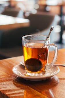Glasmok hete thee bij een koffie met vage achtergrond. natuurlijk licht