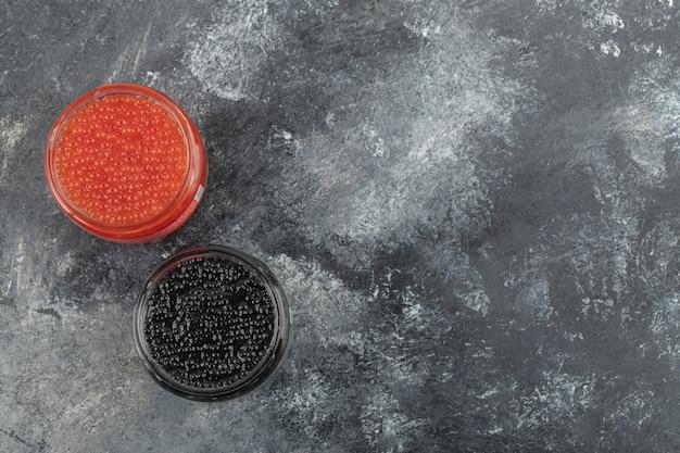 Glasplaten vol rode en zwarte kaviaar op een marmeren tafel.
