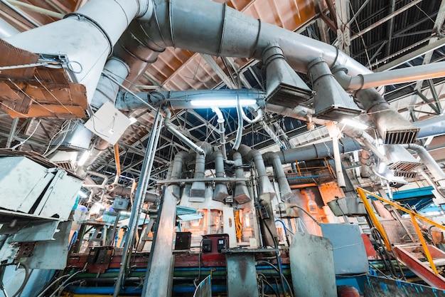 Glasproductiearbeider die met de industrieapparatuur aan fabriek werken