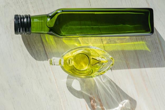 Glassausboot met extra vergine olijfolie en groene fles op houten tafel.