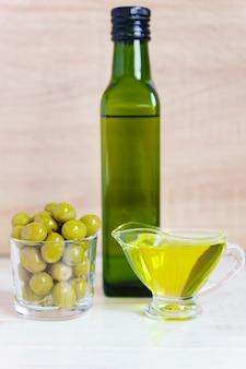 Glassausboot met extra vergine olijfolie, verse groene olijven en fles op houten tafel.
