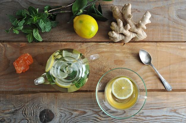 Glastheepot en glasmok thee met gember en citroen en munt op rustieke houten achtergrond