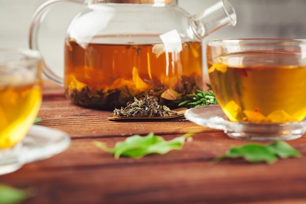 Glastheepot met kop van zwarte thee op houten lijst