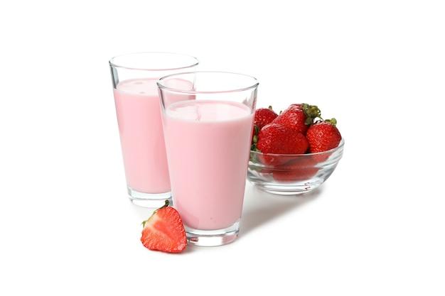 Glazen aardbeienmilkshake en ingrediënten die op witte achtergrond worden geïsoleerd