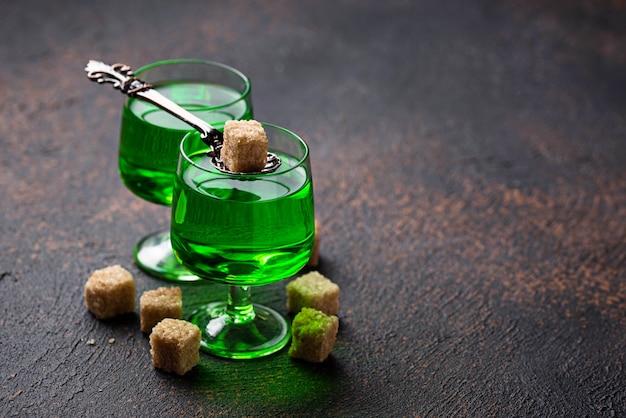 Glazen absint met bruine suiker