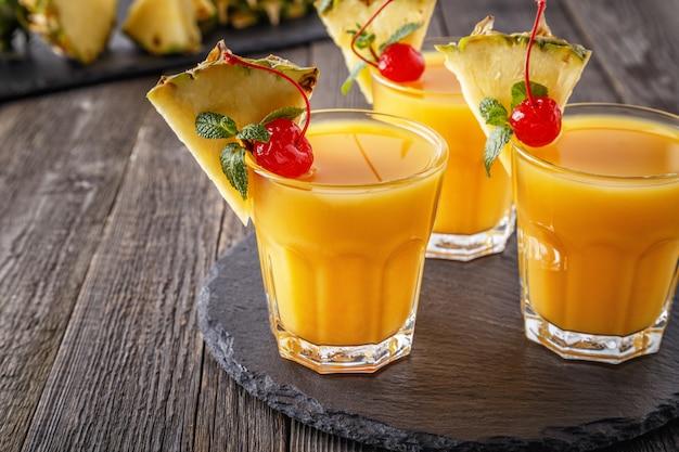 Glazen ananassap met stukjes ananas, cocktail cherry en mint op houten tafel.