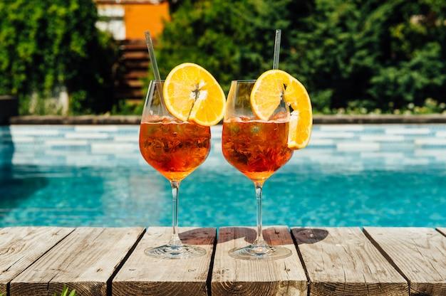 Glazen aperol spritz cocktail op het zwembad