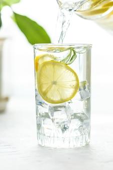 Glazen beker en een karaf water, ijs, munt en citroen op een witte tafel