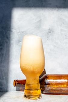 Glazen beker geserveerd met ipa-bier en een fles en een blikje aan de onderkant