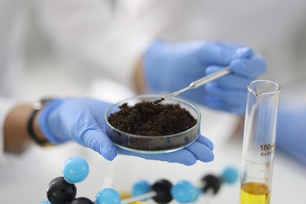 Glazen beker met bodemmonster staat op hand in rubberen handschoen in chemisch laboratorium close-up. biochemische analyse van bodemconcept.