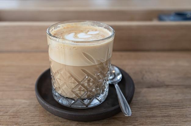 Glazen beker met cappuccino op houten tafel in café