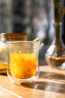 Glazen beker met duindoornthee en theepot op houten tafel in café traditionele warme herfstdrank