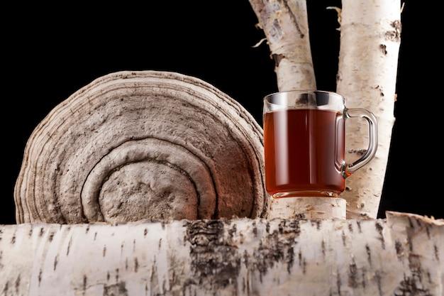 Glazen beker met een geneeskrachtige aftreksel van chaga berkenzwam. thee of koffie met chaga-paddenstoelen.
