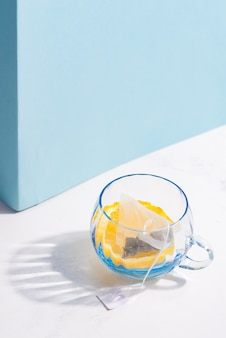 Glazen beker met fruit theezakje en schijfje citroen op een witte tafel