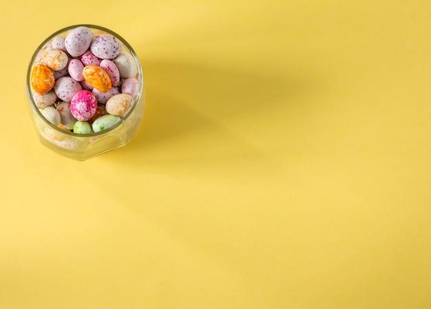 Glazen beker met gekleurde snoepjes bovenaanzicht