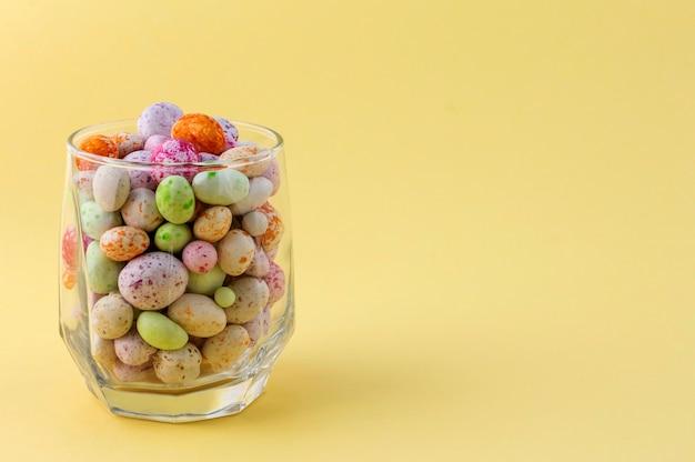 Glazen beker met gekleurde snoepjes.