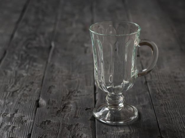 Glazen beker met handvat op houten tafel