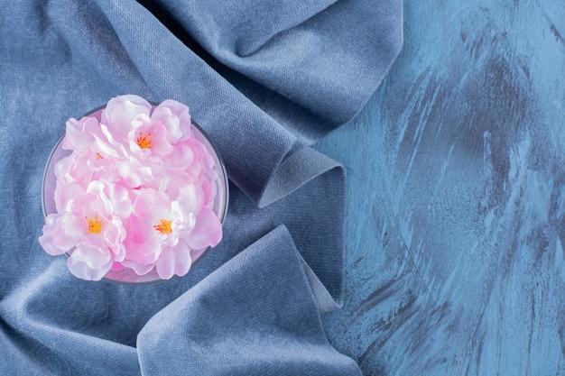 Glazen beker met roze bloemblaadjes op blauw.