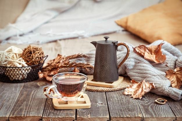 Glazen beker met thee en theepot op houten tafel met herfst decor details close-up.