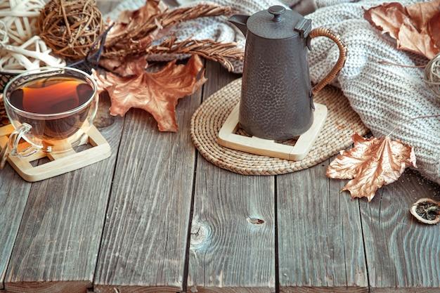 Glazen beker met thee en theepot op houten tafel met herfst decor details kopie ruimte.