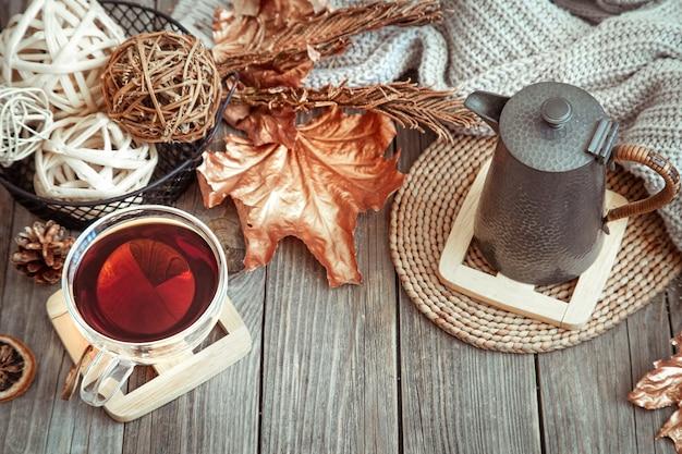 Glazen beker met thee en theepot op houten tafel met herfst decor details.