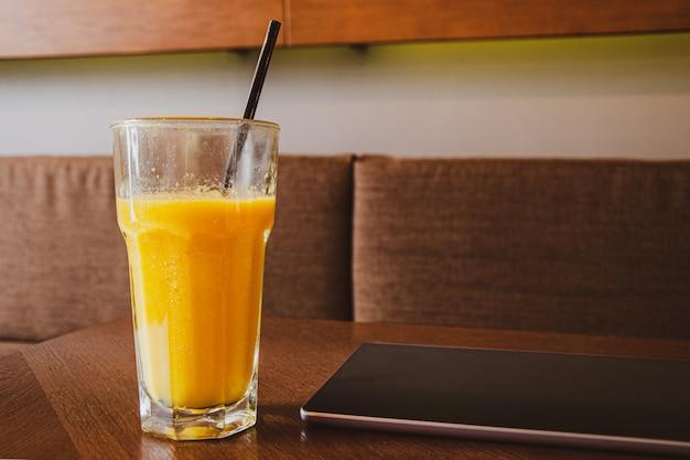 Glazen beker met vers geperst sinaasappelsap en tablet op tafel in café