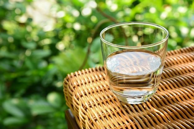 Glazen beker met water op een rieten tafel over de aard
