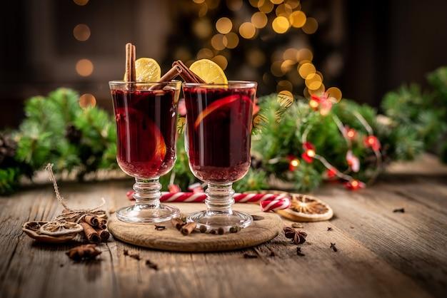 Glazen bekers met aromatische rode glühwein staande op houten plaat op kerstmis