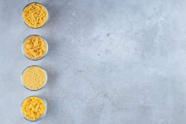 Glazen bekers vol met verschillende soorten rauwe droge pasta op een stenen achtergrond.