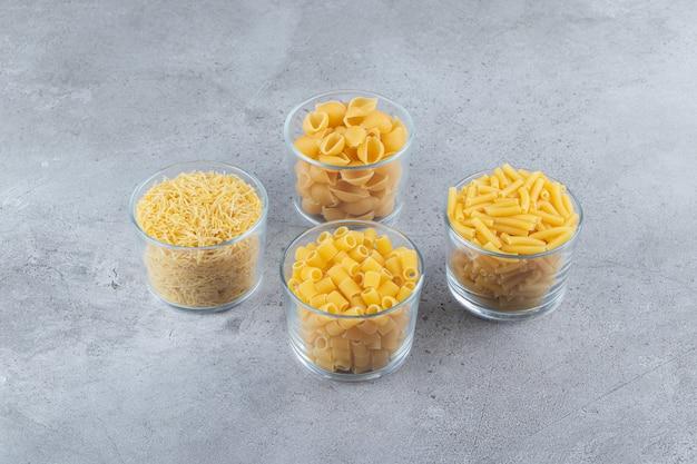 Glazen bekers vol met verschillende soorten rauwe droge pasta op een stenen ondergrond. Premium Foto
