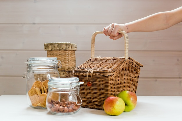 Glazen blikjes met noten en koekjes en appels op houten tafel nul afval picknick concept