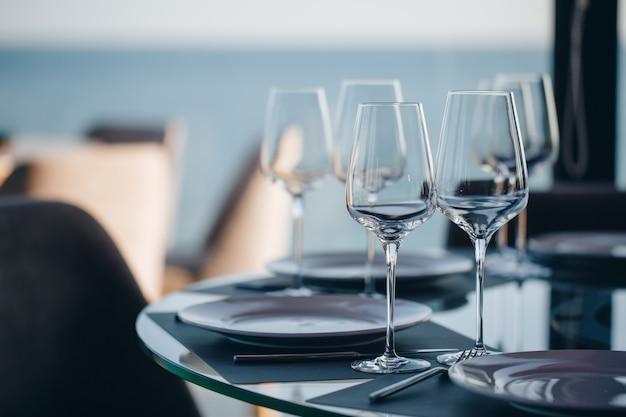 Glazen, bloemvork, mes geserveerd voor het diner in restaurant met gezellig interieur