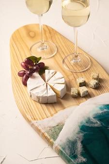 Glazen champagne, kaas en wijn op een prachtig exclusief bord versierd met epoxyhars in de vorm van zeegolven. Premium Foto
