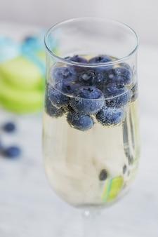 Glazen champagne met bosbessen en groene bitterkoekjes