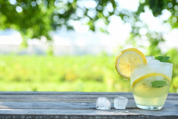 Glazen citroensap op een houten tafel, zomer set, outdoor hebzucht blured, boke. water detox