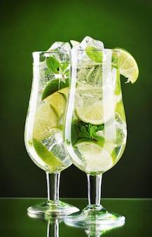 Glazen cocktails met limoen en munt op groene ruimte