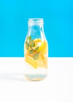 Glazen container gevuld met plakjes sinaasappel en water