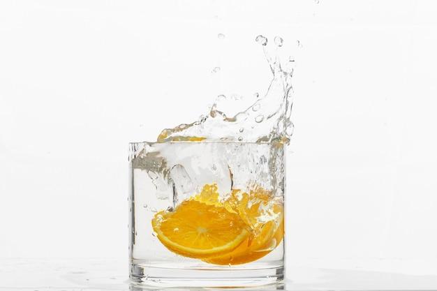 Glazen container met vloeibare gevallen sinaasappelschijfjes scheutje water op een witte achtergrond