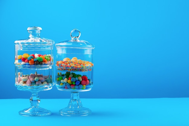 Glazen containers met kleurrijke snoepjes tegen blauwe achtergrond close-up