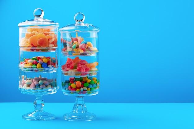 Glazen containers met kleurrijke snoepjes tegen blauwe achtergrond