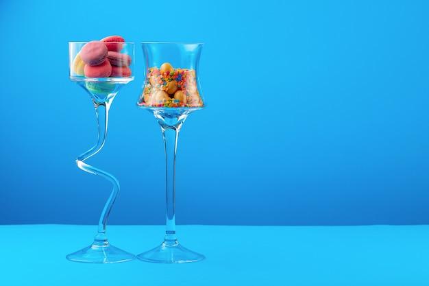 Glazen containers met kleurrijke snoepjes tegen blauwe close-up