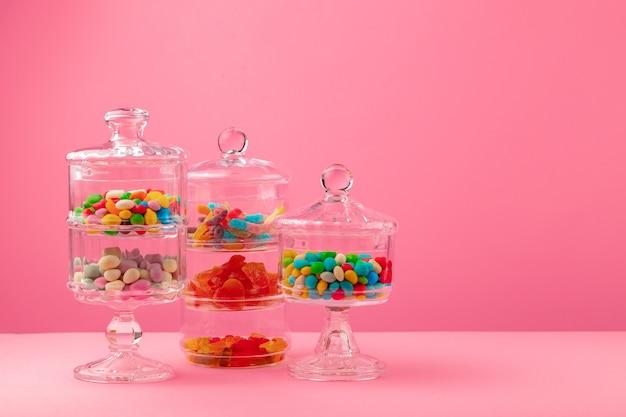 Glazen containers met snoep en snoep tegen roze