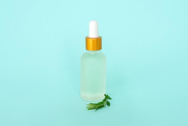 Glazen cosmetik fles met olie. container voor een product voor vrouwen met kleine witte bloemen op een turquoise achtergrond. cosmetische pot. plaats voor tekst