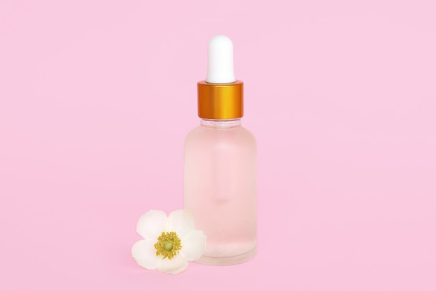 Glazen cosmetikfles met olie. container voor een product voor vrouwen met kleine witte bloemen op een turquoise achtergrond. cosmetische pot. plaats voor tekst