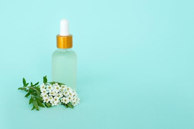 Glazen cosmetische fles met olie. container met kleine witte bloemen. cosmetische pot.