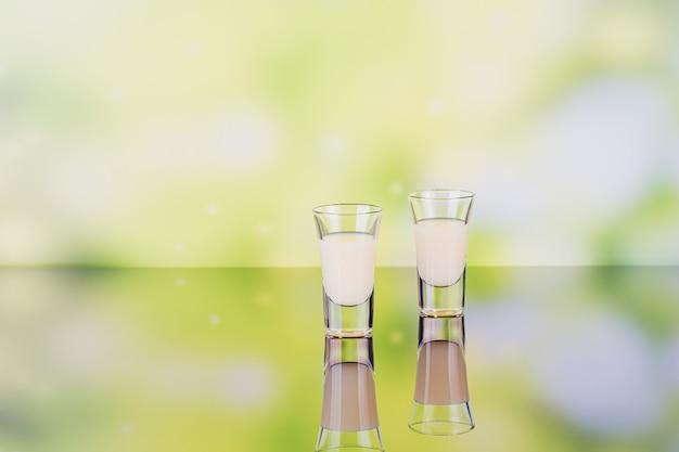 Glazen crème likeur op groene achtergrond met reflectie. kort van citroenlikeur. traditionele italiaanse alcoholische drank limoncello