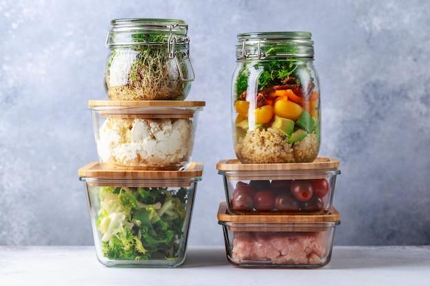 Glazen dozen en blikken met vers voedsel koelkast opslag concept overgieten